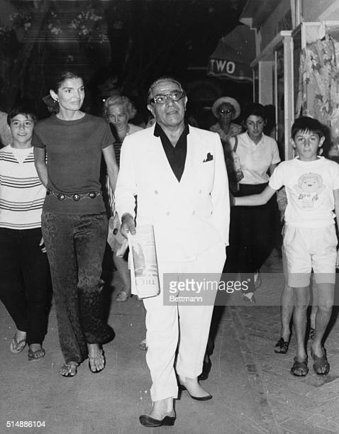 Jackie and Aristotle Onassis walk through the streets of a town on Capri followed by local residents