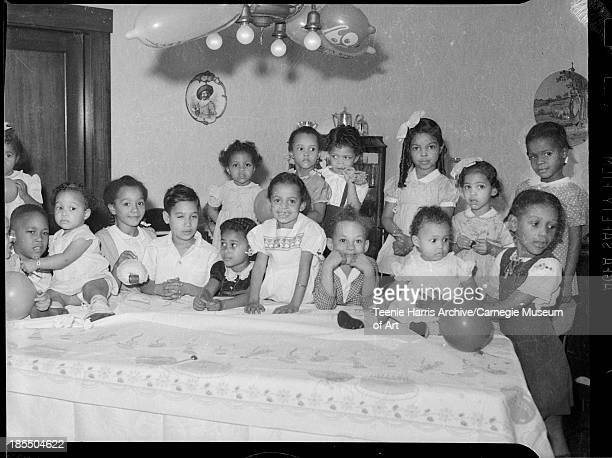 Jackie Ann Hamilton surrounded by boys and girls gathered behind table with birthday cake patterned tablecloth in Hamilton's home Anaheim street for...