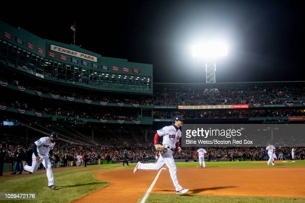 Jackie Bradley Jr #19 and Andrew Benintendi of the Boston Red Sox run onto the field before game two of the 2018 World Series against the Los Angeles...