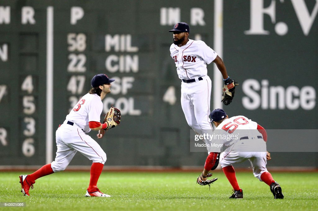 Jackie Bradley Jr. #19, Andrew Benintendi #16 and Mookie Betts #50 of the Boston Red Sox celebrate after defeating the Toronto Blue Jays 6-1 at Fenway Park on September 6, 2017 in Boston, Massachusetts.