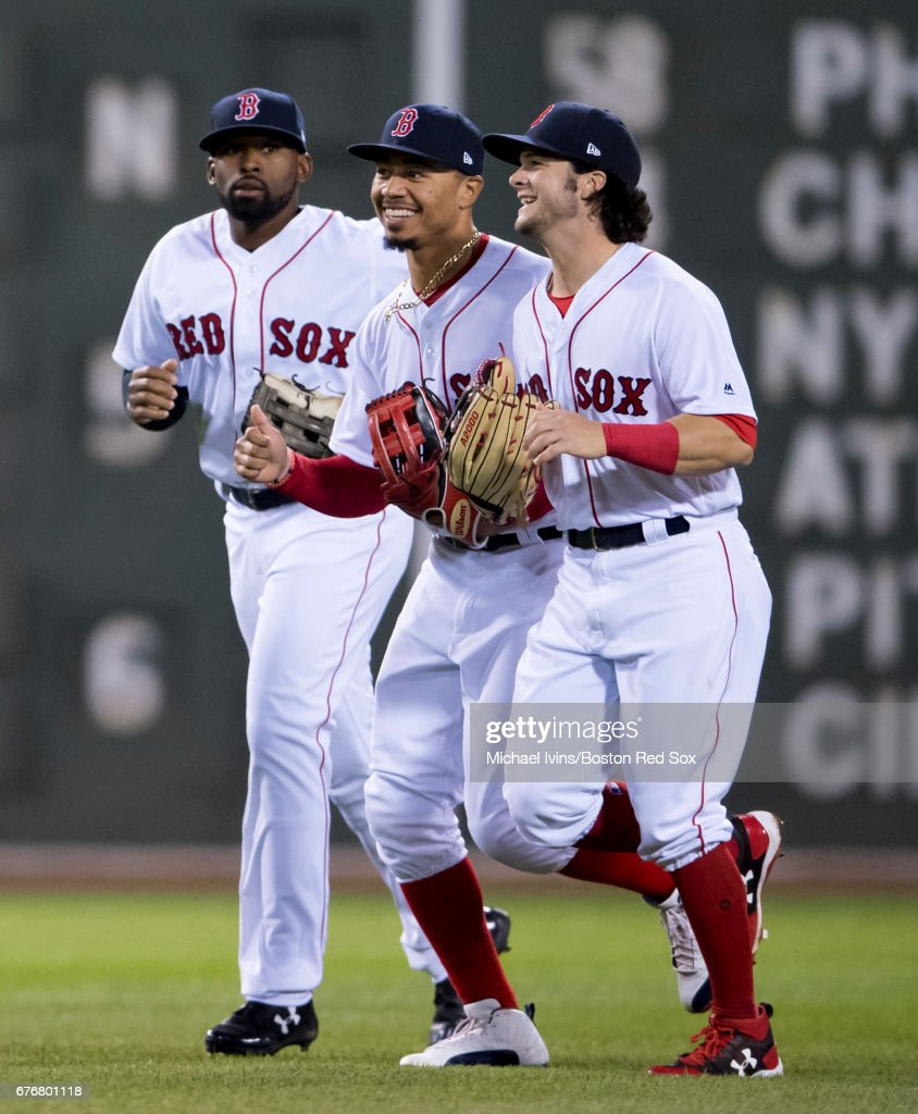 Jackie Bradley Jr. #19, Mookie Betts #50 and Andrew Benintendi #16 of the Boston Red Sox run off the field after a 5-2 win over the Baltimore Orioles at Fenway Park on May 2, 2017 in Boston, Massachusetts.