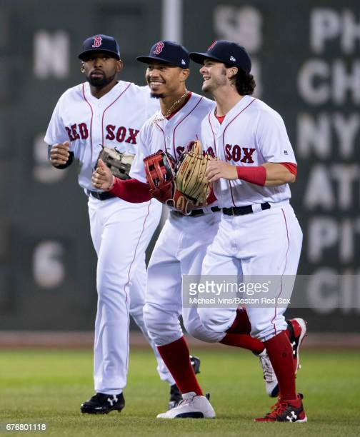 Jackie Bradley Jr #19 Mookie Betts and Andrew Benintendi of the Boston Red Sox run off the field after a 52 win over the Baltimore Orioles at Fenway...