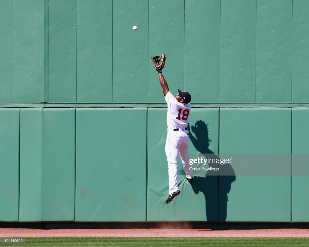 Jackie Bradley Jr. #19 of the Boston Red Sox atempts to catch a ball in the oufield in the top of the sixth inning during the game against the Kansas City Royals at Fenway Park on July 30, 2017 in Boston, Massachusetts.