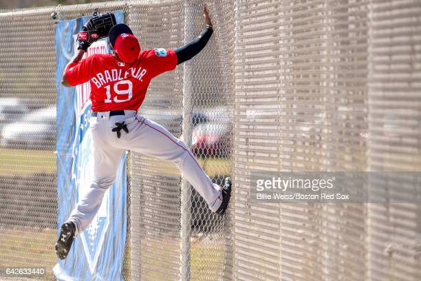 Jackie Bradley Jr #19 of the Boston Red Sox catches a fly ball as he climbs the fence during a team workout on February 18 2017 at Fenway South in...