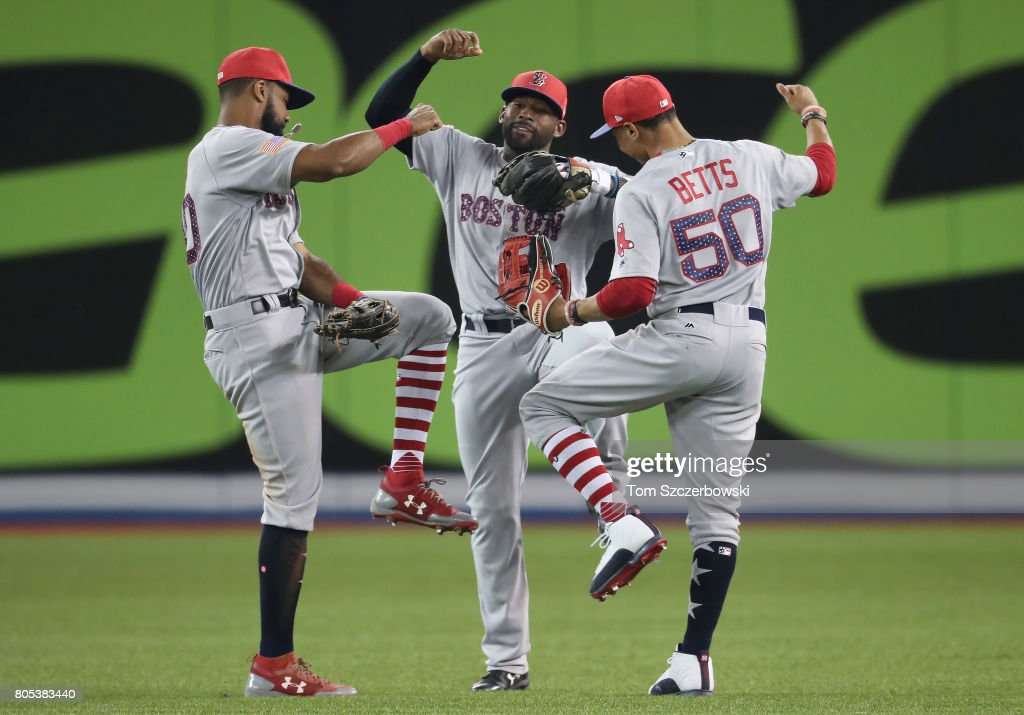 Jackie Bradley Jr. #19 (C) of the Boston Red Sox celebrates their victory with Chris Young #30 and Mookie Betts #50 during MLB game action against the Toronto Blue Jays at Rogers Centre on July 1, 2017 in Toronto, Canada.