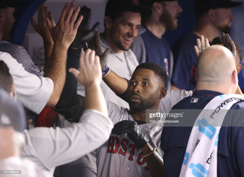 Jackie Bradley Jr. #19 of the Boston Red Sox is congratulated by teammates in the dugout after hitting a two-run home run in the 10th inning during MLB game action against the Toronto Blue Jays at Rogers Centre on August 7, 2018 in Toronto, Canada.