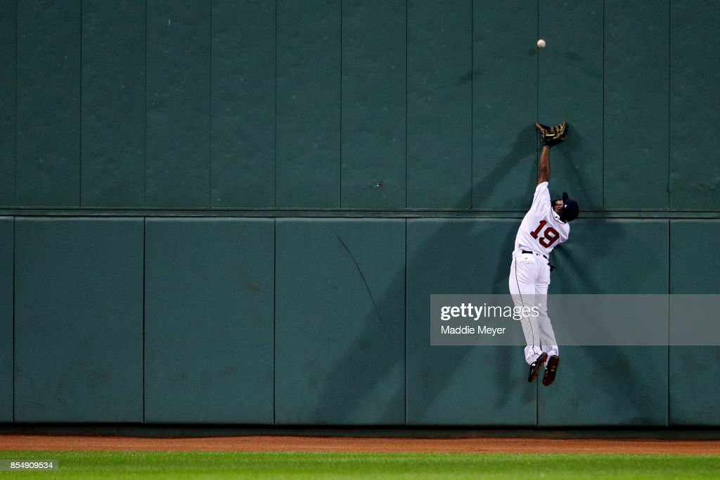 Jackie Bradley Jr. #19 of the Boston Red Sox jumps for a double hit by Ryan Goins #17 of the Toronto Blue Jays that bounced off of the wall during the ninth inning at Fenway Park on September 27, 2017 in Boston, Massachusetts.