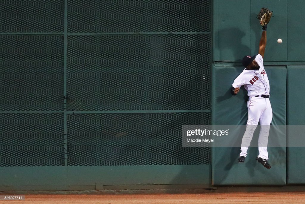 Jackie Bradley Jr. #19 of the Boston Red Sox reaches for a double hit by Jed Lowrie #8 of the Oakland Athletics during the first inning at Fenway Park on September 12, 2017 in Boston, Massachusetts.