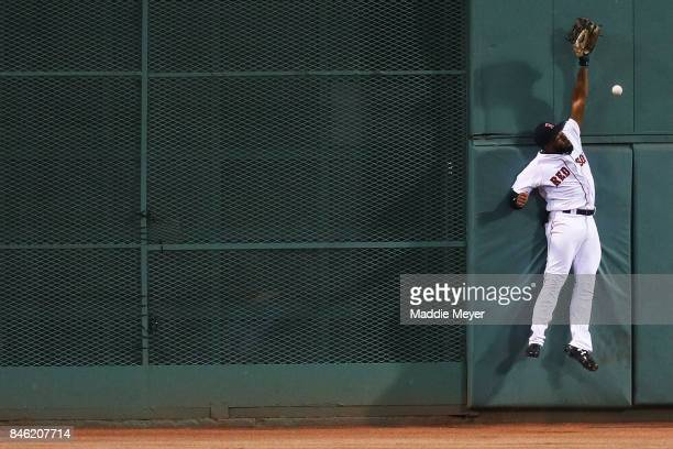 Jackie Bradley Jr #19 of the Boston Red Sox reaches for a double hit by Jed Lowrie of the Oakland Athletics during the first inning at Fenway Park on...