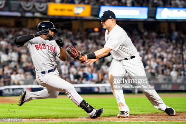Jackie Bradley Jr. #19 of the Boston Red Sox slides as he is tagged out by Luke Voit of the New York Yankees during the third inning of game four of...