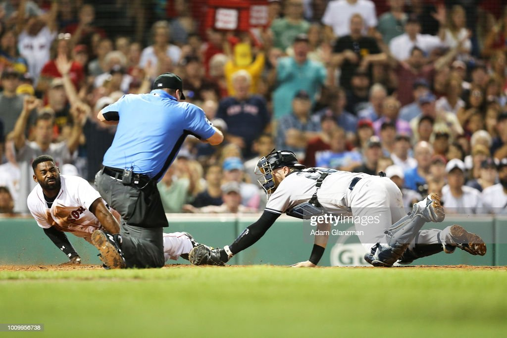 Jackie Bradley Jr. #19 of the Boston Red Sox slides safely under the tag of Austin Romine #28 of the New York Yankees in the fourth inning of a at Fenway Park on August 2, 2018 in Boston, Massachusetts.