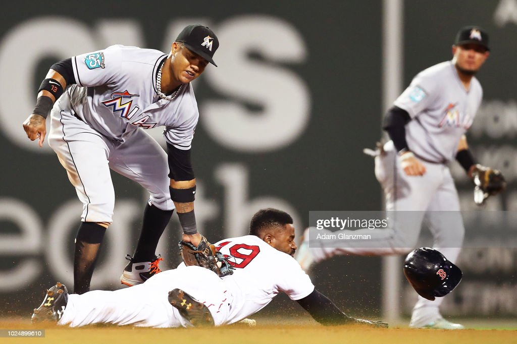 Jackie Bradley Jr. #19 of the Boston Red Sox steals second base sliding safely under the tag of Starlin Castro #13 of the Miami Marlins in the seventh inning of a game at Fenway Park on August 28, 2018 in Boston, Massachusetts.