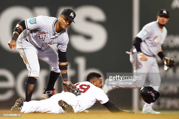 Jackie Bradley Jr #19 of the Boston Red Sox steals second base sliding safely under the tag of Starlin Castro of the Miami Marlins in the seventh...