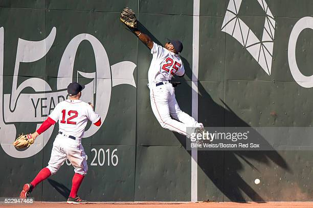 Jackie Bradley Jr #25 of the Boston Red Sox attempts to catch a fly ball off the Green Monster as Brock Holt looks on during the eighth inning of a...