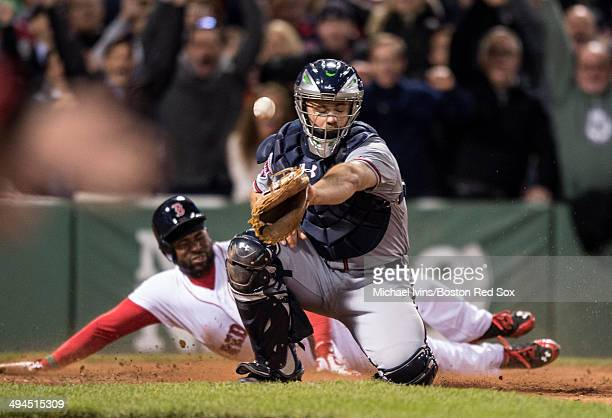 Jackie Bradley Jr. #25 of the Boston Red Sox dives into home with the game-winning run ahead of a throw to Evan Gattis of the Atlanta Braves in the...