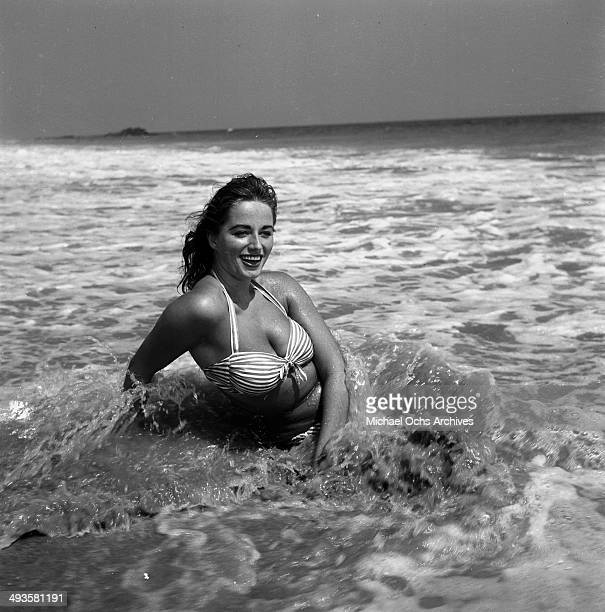 Jackie Collins poses in the ocean in Los Angeles California