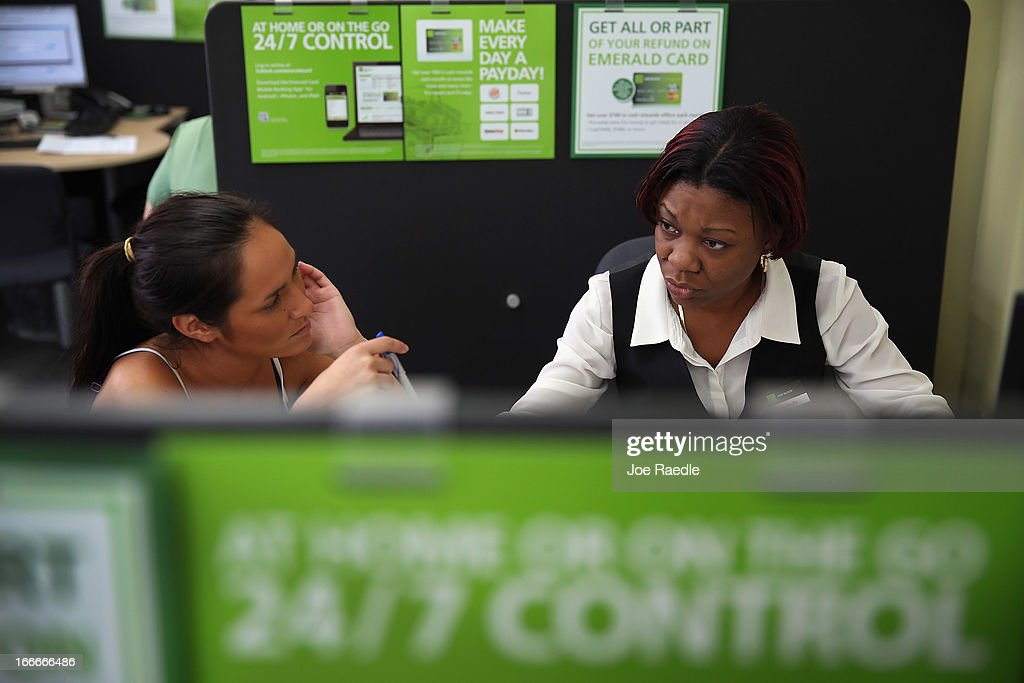 Jackie Duong (L) sits with Sandra Johnson Darby, tax associate, as she does her taxes at the H&R Block office on April 15, 2013 in Miami Beach, Florida. With the U.S. tax deadline of midnight April 15 rapidly approaching, last-minute filers are rushing to get their returns done.