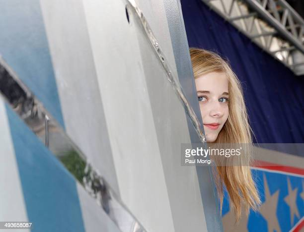 Jackie Evancho peeks around the corner to see what's happening onstage at the 25th National Memorial Day Concert rehearsals at US Capitol West Lawn...