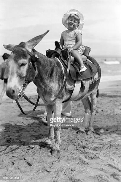 Jackie Garai daughter of Alexandre Garai founder of Keystone press agency enjoying a donkey ride on a beach in August 1932 in Deauville France