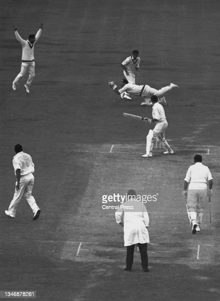 Jackie Hendriks, wicketkeeper for the West Indies makes a diving catch to dismiss England batsman Tom Graveney for 32 runs off a delivery by Charlie...