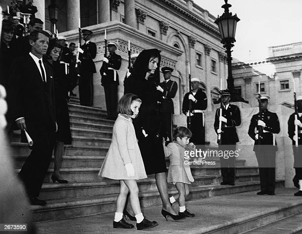Jackie Kennedy and her children John Jr and Caroline walking down steps past a guard of honour at the funeral of President Kennedy Robert Kennedy is...