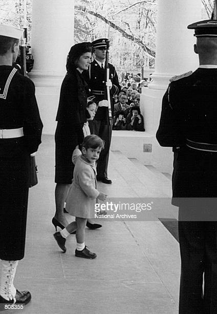 Jackie Kennedy waits for the arrival of the casket containing the body of her husband John F Kennedy with her children John and Caroline at the White...