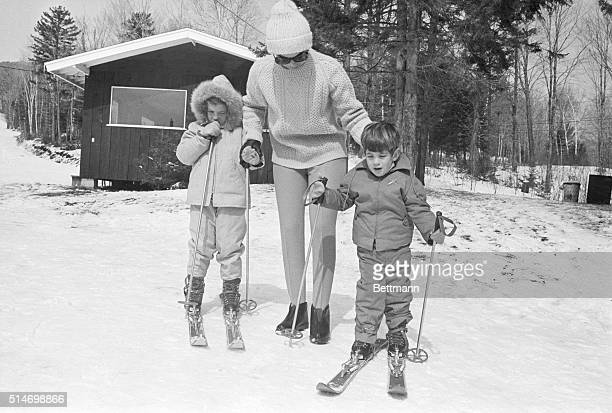 Jackie Kennedy widow of the late President John F Kennedy stands with her children Caroline and John Jr as they try out their skis on Mount Mansfield...