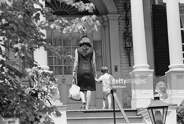Jackie Kennedy widow of the late President John F Kennedy walks with her son John Jr into their Georgetown home