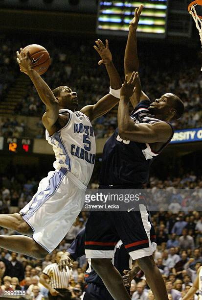 Jackie Manuel of the University of North Carolina Tar Heels goes up to dunk over Emeka Okafor of the University of Connecitcut Huskies during the...