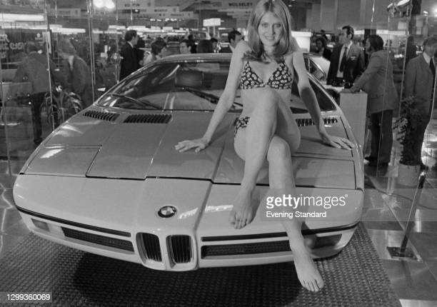 Jackie Matcham poses on a BMW E25 Turbo concept car at the British International Motor Show in Earl's Court, London, UK, October 1972.