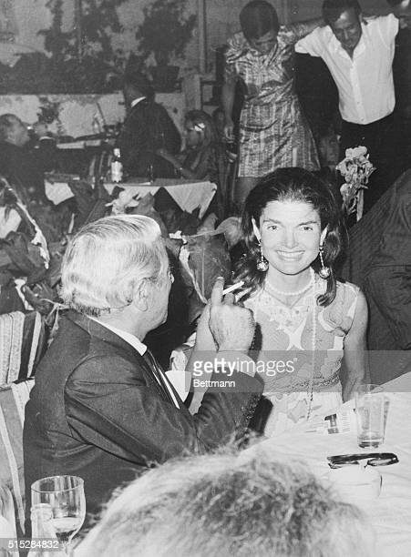 "Jackie Onassis smiles at photographer while her husband, Aristotle, admires the ""syrtake"" skill of some of his friends dancing , at a party..."