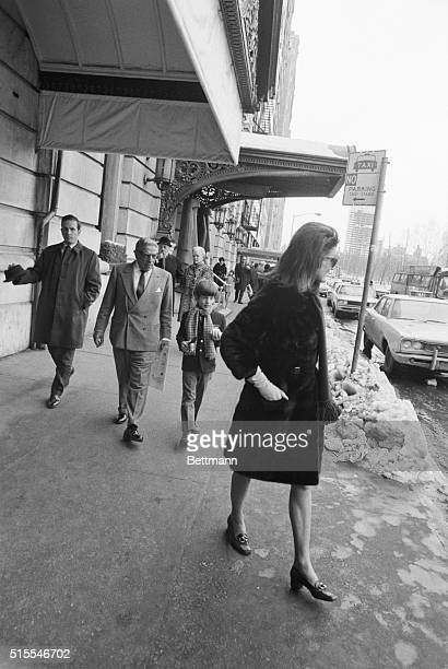 Jackie Onassis walks along a sidewalk by the Plaza Hotel, followed by her husband Aristotle and her son, JFK Jr.