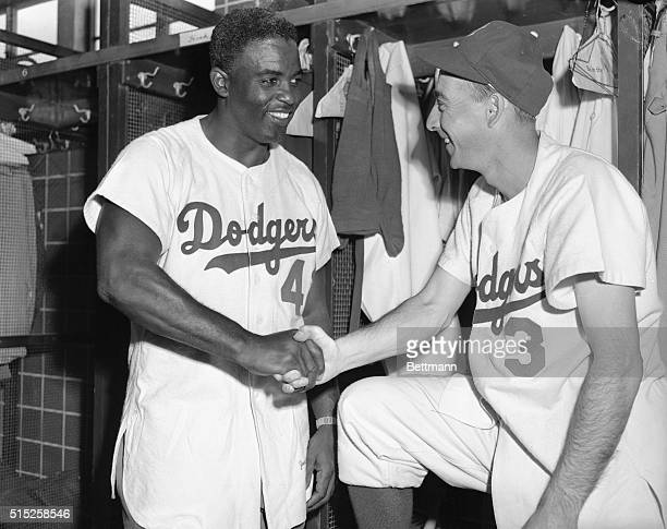 Jackie Robinson and Billy Cox, of the Brooklyn Dodgers, are shown shaking hands in the Dodger Clubhouse at Vero Beach to counter-act the rumors that...