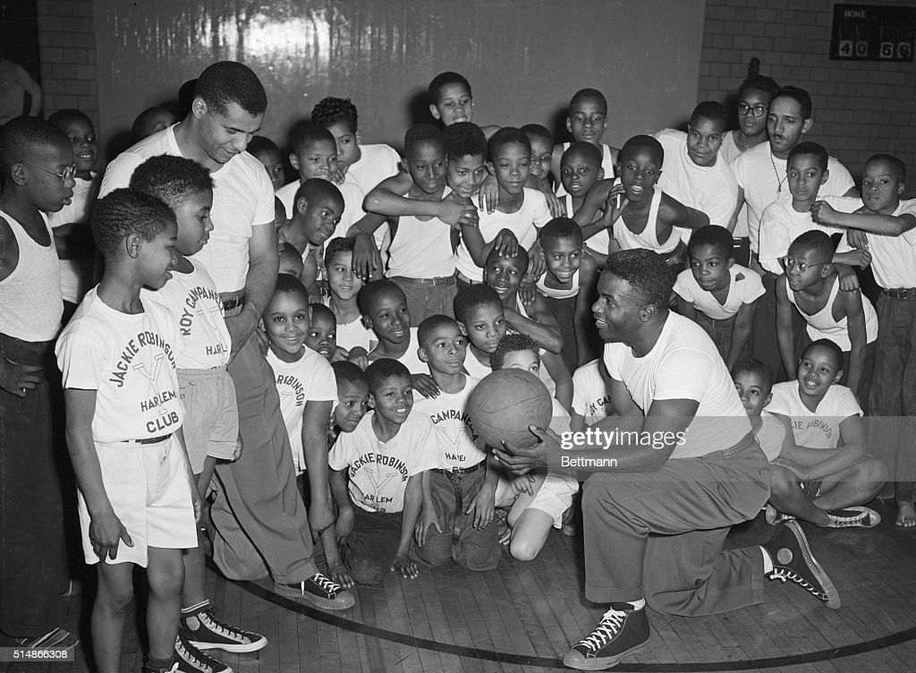 Jackie Robinson (kneeling) and Roy Campanella of the Brooklyn Dodgers teach basketball to a group of young boys at the YMCA in Harlem.