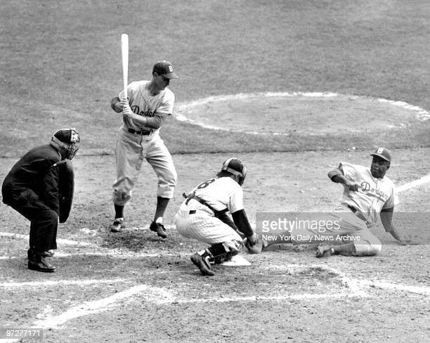 Jackie Robinson Brooklyn Dodgers tries to steal home during World Series against the New York Yankees Yankee Catcher Yogi Berra has the ball and...