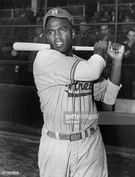 Jackie Robinson, first African Amercian to be signed up by a Major League baseball team, is shown in post-swing position in front of the stands....