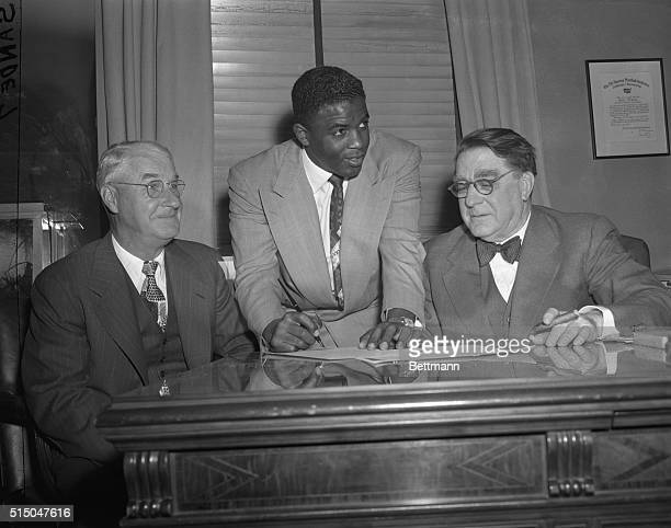 Jackie Robinson, first African-American to play in the Major Leagues signs his 1949 contract as Branch Rickey , Brooklyn Dodgers President, and...