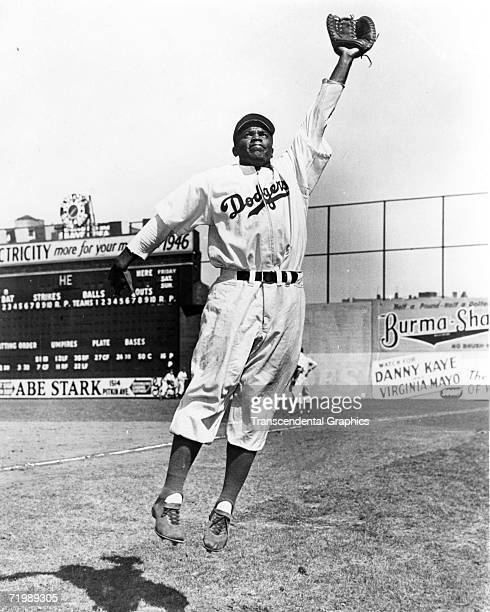 Jackie Robinson, first baseman for the Brooklyn Dodgers, leaps for a throw during warm ups before a game in 1947 at Ebbets Field.