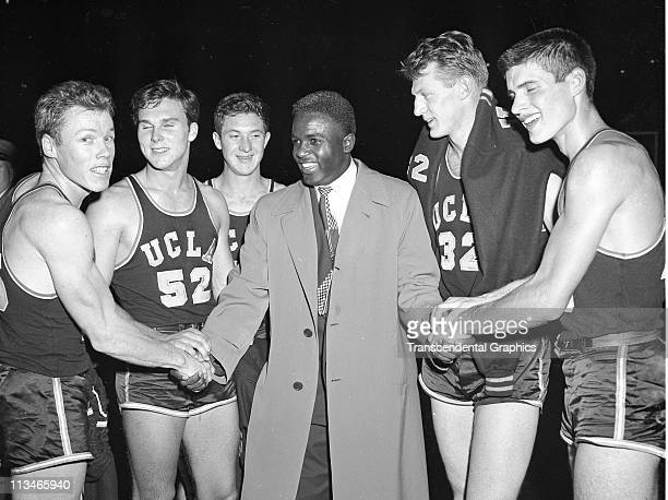 Jackie Robinson greets the members of the UCLA basketball team after defeating City College of New York on December 28, 1949 in New York City.