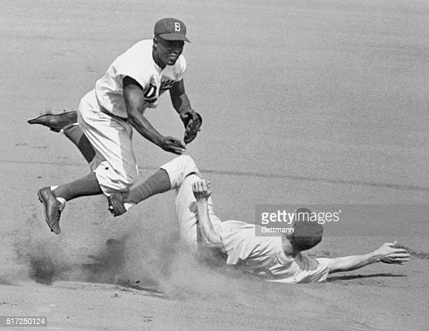Jackie Robinson leaps into the air in an attempt to make a double play as Hank Sauer slides into second. The action took place during the second...