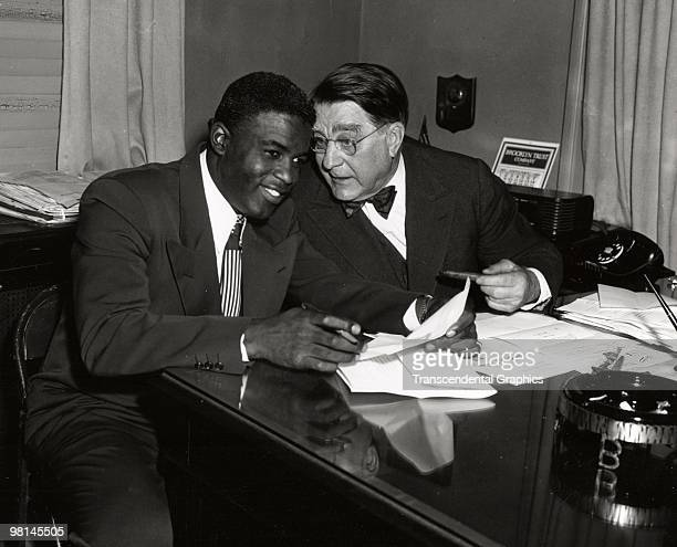 Jackie Robinson left and Branch Rickey share a joke during a contract signing session in the front offices of the Brooklyn Dodgers at Ebbets Field in...