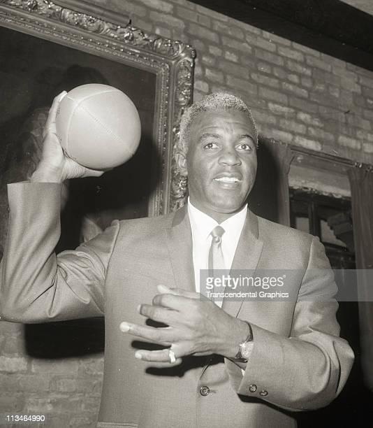 Jackie Robinson named General Manager of the Brooklyn Dodgers football team poses with a football on May 3 1966 in the Brooklyn borough of New York...