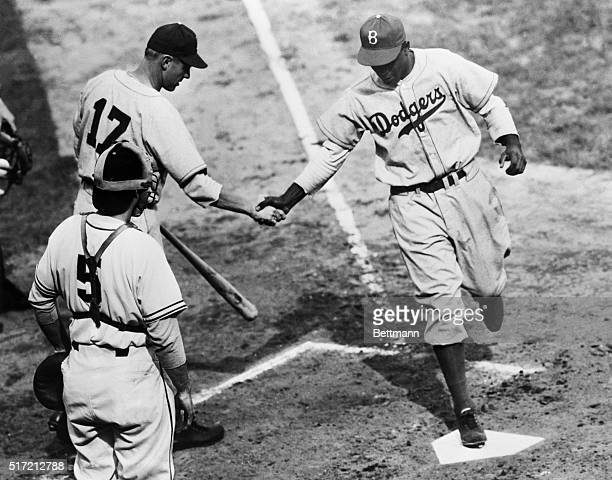 Jackie Robinson of the Brooklyn Dodgers, breaking the color barrier this season as the first African-American to play in the Major Leagues, crosses...