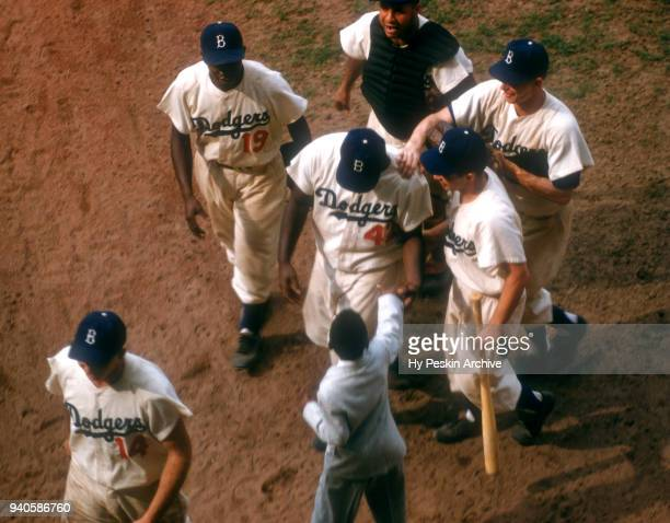 Jackie Robinson of the Brooklyn Dodgers is greeted by a young child as his teammates Jim Gilliam Roy Campanella Pee Wee Reese Gil Hodges and the bat...