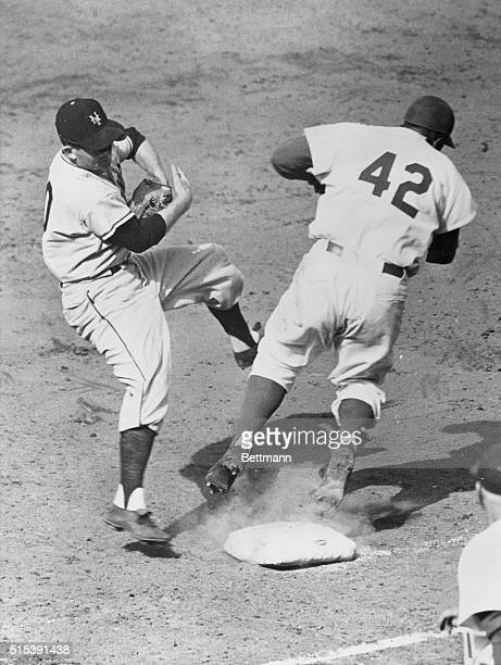 Jackie Robinson of the Brooklyn Dodgers overruns first base and inadvertently runs into Davey Williams of the New York Giants
