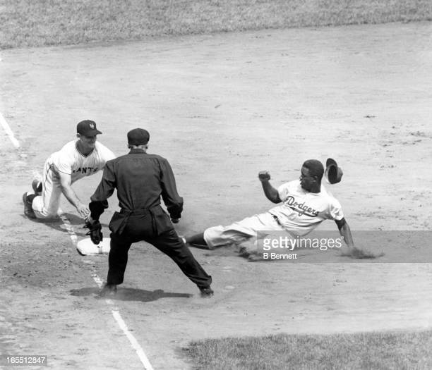 Jackie Robinson of the Brooklyn Dodgers slides safely into third as Sid Gordon of the New York Giants was late to tag Robinson as home plate umpire...