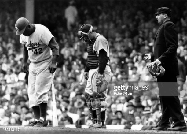 Jackie Robinson of the Brooklyn Dodgers steps out of the batters box as catcher Yogi Berra of the New York Yankees looks down during the 1955 World...