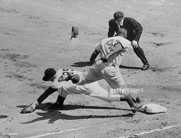 Jackie Robinson of the Dodgers is minus his cap as he reaches for first base too late in first inning action of today's season opener against the New...