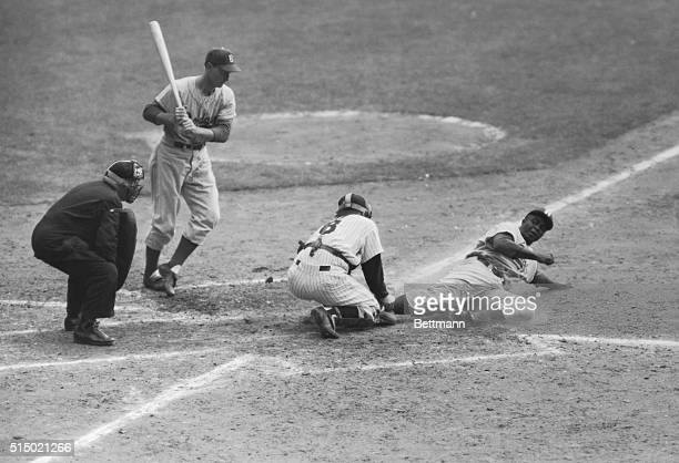 Jackie Robinson of the Dodgers slides home safely on his steal in the eighth inning of this series opener at Yankee Stadium. This was the play that...