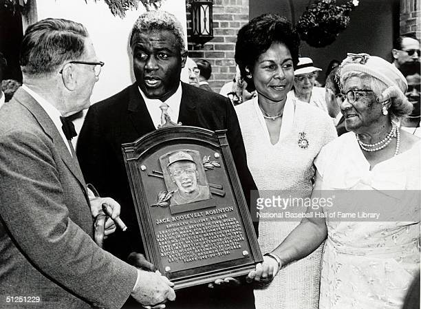 Jackie Robinson poses with his family and the National Baseball Hall of Fame Inductee plaque Jackie Robinson played for the Brooklyn Dodgers from...